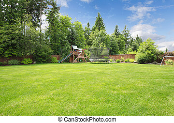 Summer fenced backyard with play ground area and trees and large lawn.