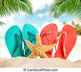 Summer flipflops on sandy beach, blur sea on background. ...