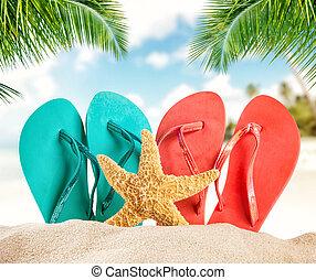 Summer flipflops on sandy beach, blur sea on background. ...