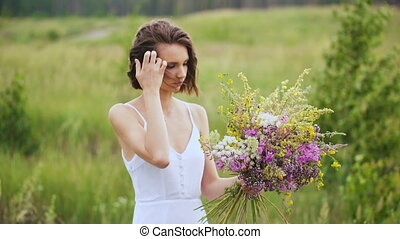 Summer flowering field and a beautiful girl in a white sundress. Brunette collects floral arrangement of wild flowers.