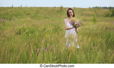 Summer flowering field and a beautiful girl in a white sundress. The slender young brunette holding a huge bouquet of wildflowers