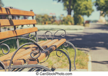 Summer footpath in the city park with a bench on a sunny day. Toned photo. Shallow depth of the field.