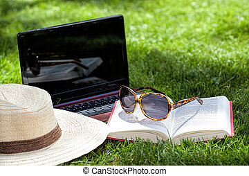 Hat, book, sunglasses and notebook on a grass