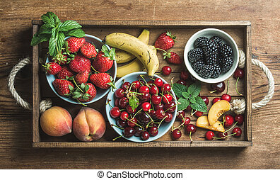 Summer fresh fruit and berry variety in rustic wooden tray