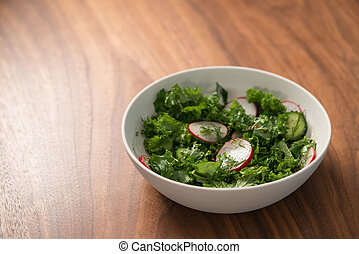 Summer fresh salad with radish, cucumber and herbs in white bowl