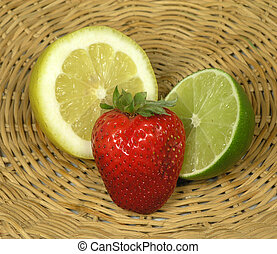 Cut lemon, lime and whole strawberry on a straw platter