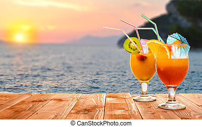 Summer fruit drinks or juice with ocean beach on background