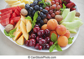 Colorful summer fruit platter with pineapple, watermelon, cherries, apricots, strawberries, cantaloupe, walnuts and mint