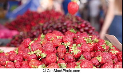 Close up of a pile of red ripe juicy strawberries with green rootlets and a price tag. Organic produce concept. Life camera