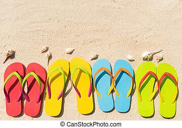 Summer fun - Four pairs of flip flops in a row on beach