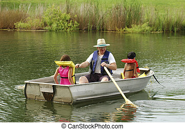 Summer Fun with Grandpa - A senior man rowing his two young...