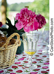 summer garden party table with bread in wicker basket, tasty lemonade and pink peonies