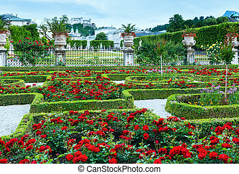 Summer Gardens of Mirabell Palace with red rose flowerbeds and Hohensalzburg Fortress behind (Salzburg, Austria)
