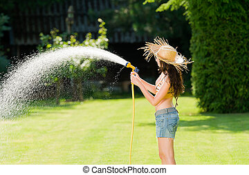 Summer garden grass woman play with water hose sunny day