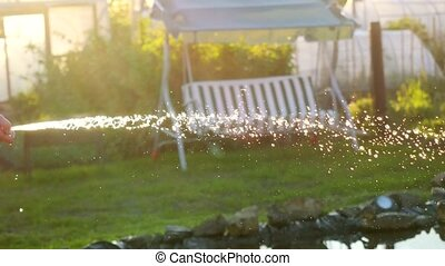 Summer gardener smiling woman watering watering flowers and plants during sunset sunny day