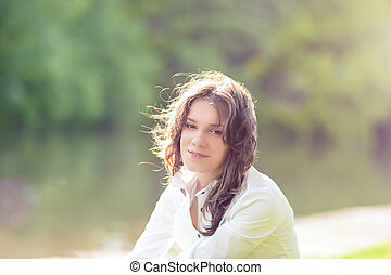 Summer Girl Portrait. Caucasian Brunette Woman Smiling Happilly on Sunny Day Outdoors in Park. Horizontal Image