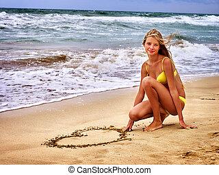 Summer girl sea. Girl in swimsuit write on sand heart shape .