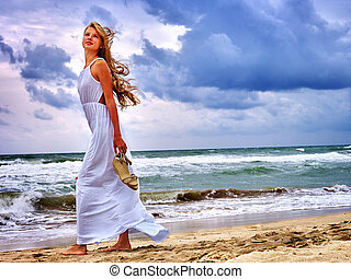 Girls goes on coast near beach sea.