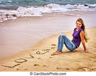 Teenager draw love on sand near waves.