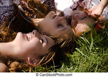 Happy Teenagers girls friends in national dress in green grass on summer day