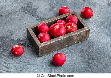 Summer harvested red radish. Growing organic vegetables, in wooden box, on gray background