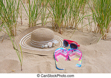 summer hat and sandals in beach sand