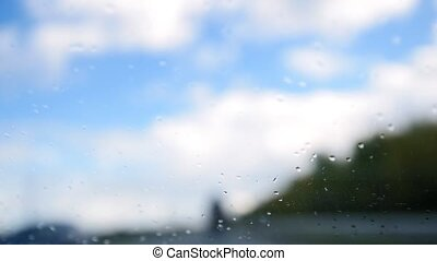 Summer highway on a rainy day - defocused background. Waterdrops in the windshield