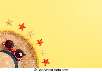 summer holiday beach background with accessories on yellow table, top view with copy space. vacation concept