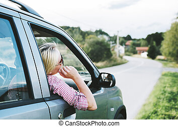 Summer holiday roadtrip travel to countryside. Young hipster blond woman driving car on rural road and having fun summer vacation.