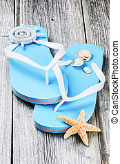 Summer holiday setting with flip flops and sea shells