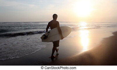 Summer holiday - Surfer holding surf board and on coast Bali...