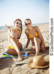 summer holiday - two attractive females on the beach