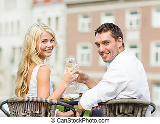 smiling couple drinking wine in cafe