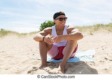 happy smiling young man sunbathing on beach towel