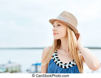 girl in hat standing on the beach
