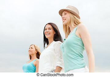 group of smiling girls chilling on the beach