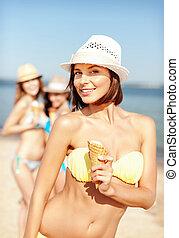 girl in bikini eating ice cream on the beach