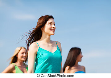 girl with friends walking on the beach