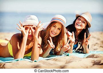 girls sunbathing on the beach - summer holidays and vacation...