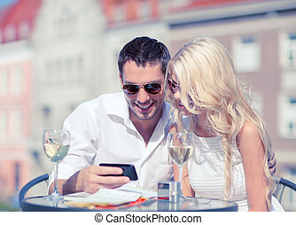 couple looking at smartphone in cafe - summer holidays,...