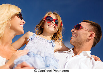 happy family in sunglasses over blue sky