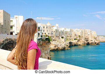 Summer holidays in Apulia. Back view of beautiful young woman in Polignano a mare town on Mediterranean Sea, Italy.