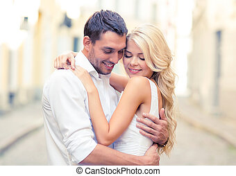 romantic happy couple hugging in the street