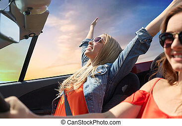 happy young women driving in convertible car