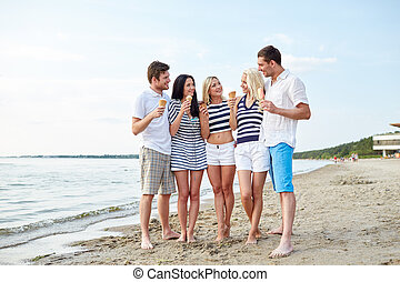friends eating ice cream and talking on beach