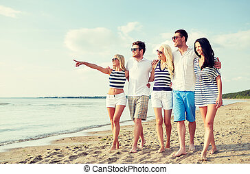 smiling friends in sunglasses walking on beach