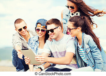 group of teenagers looking at tablet pc - summer holidays, ...