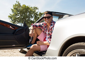 happy young man sitting in convertible car