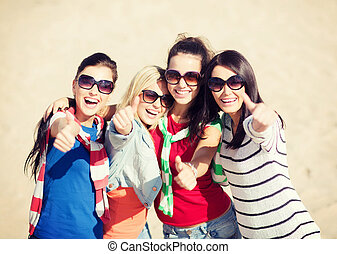summer, holidays, vacation, happy people concept - beautiful teenage girls or young women showing thumbs up