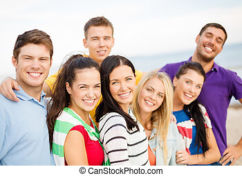 group of happy friends hugging on beach